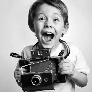 Un bambino con in mano la macchina fotografica