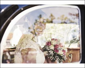 La sposa sorridente fotografata attraverso il finestrino dell'auto